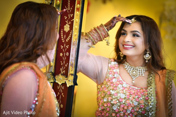 Indian bride admiring her tikka.