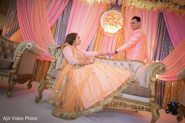 Indian couple at their engagement pink, peach and golden stage.