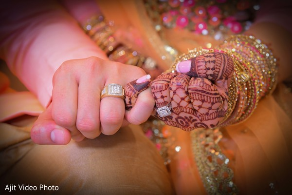 Closeup capture of Indian bride and groom's hands.