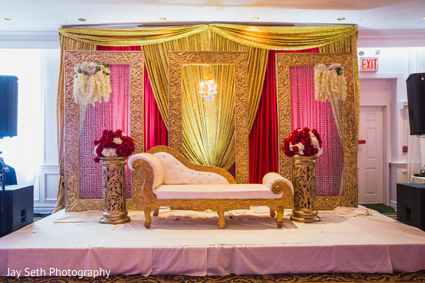 Flower and golden decorated stage for hindu reception.