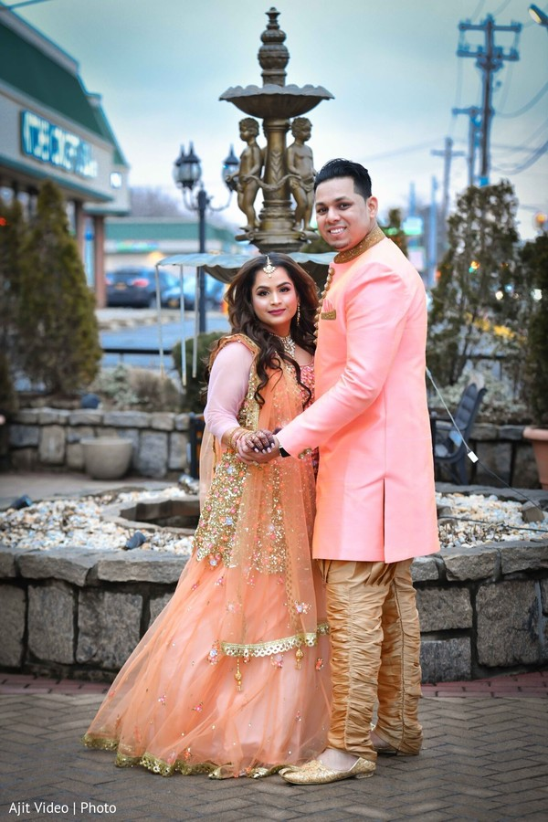 Indian couple posing outdoors for engagement photo session.
