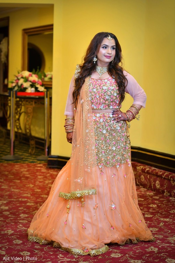 Indian bride posing on her peach and light pink color lehenga.