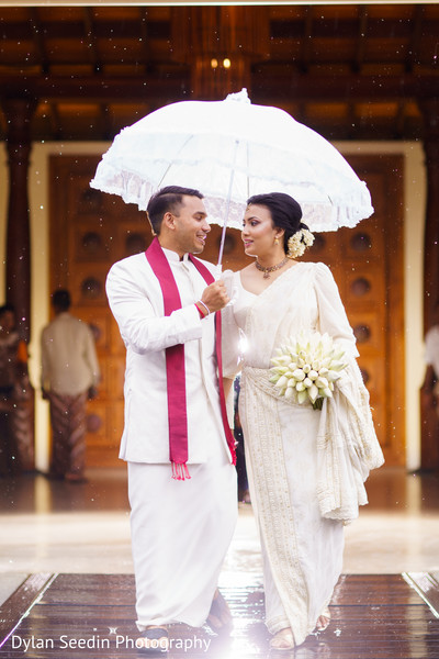 Indian groom holding the umbrella for the Maharani.