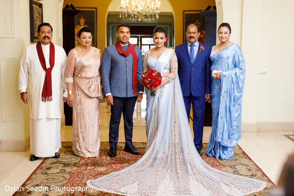 Indian newlyweds posing with both families.