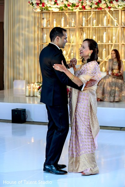 Indian groom wearing a suit and dancing with a relative.
