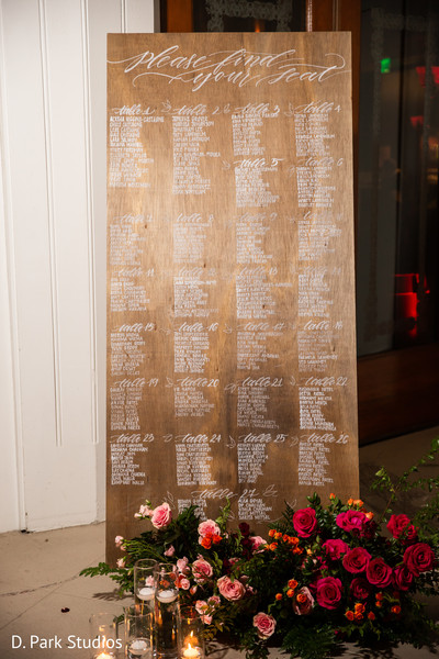 Long rectangle wooden seating chart with white letters.