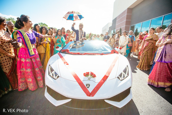 Indian groom arriving with his muscle car during baraat.