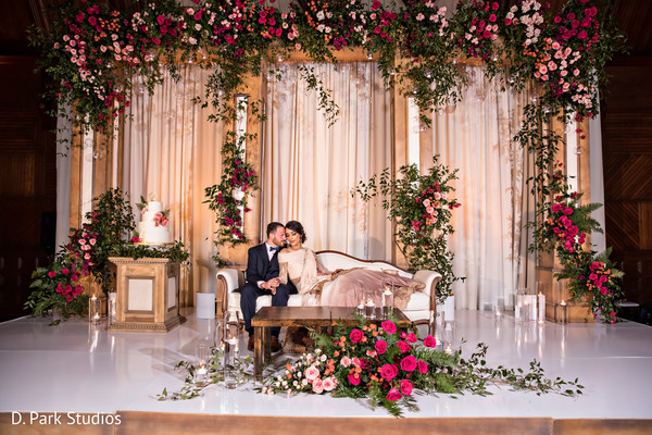 Indian couple surrounded by roses at reception stage.