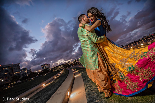 Indian couple posing outdoors with sangeet outfits.