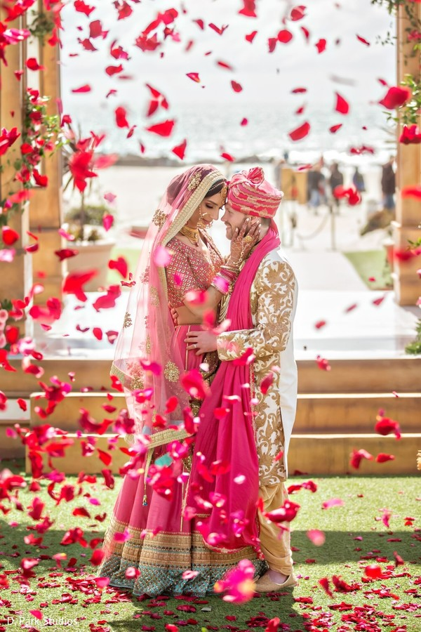 Indian couple posing on their pink and golden ceremony outfits.