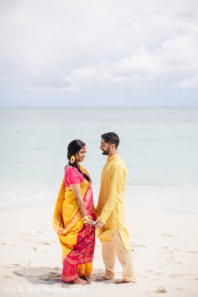 Maharani and groom gazing at each other in front of the ocean