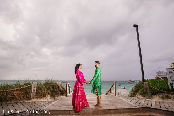 Maharani and Indian groom holding hands under a cloudy sky