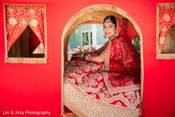 Indian bride wearing a red lengha inside a red Doli.