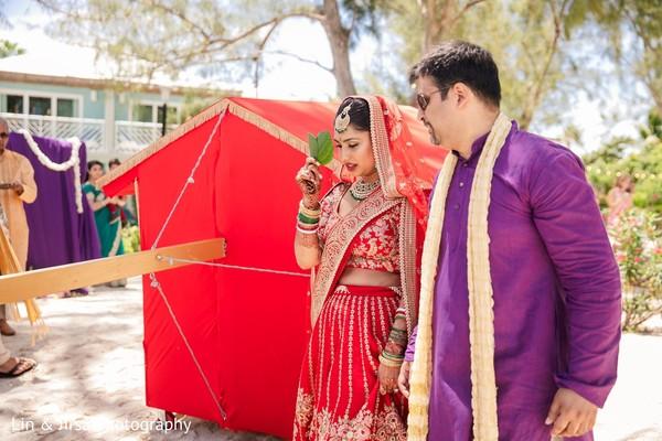 Indian bride holding a leaf besides her Indian doli.