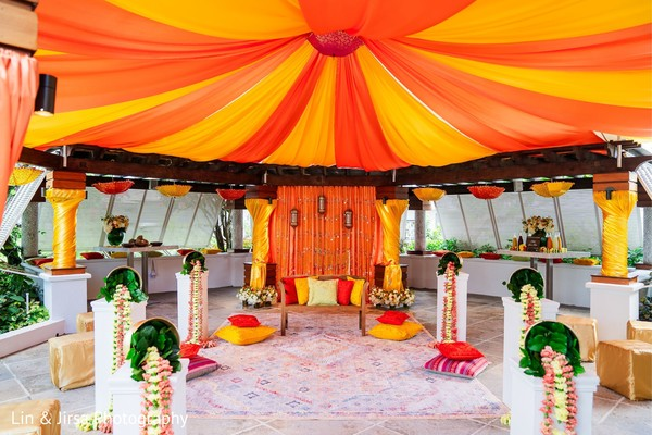 Yellow and orange drapes with floral decorations for the wedding.