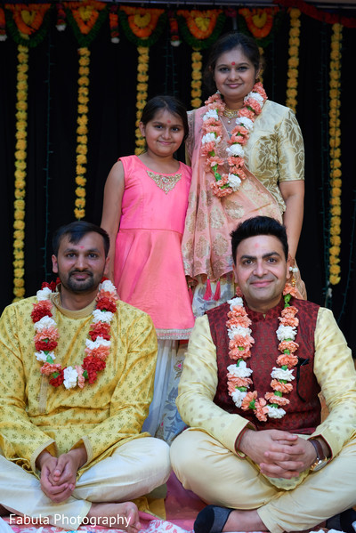 Indian groom with garland and Indian relatives during photo shoot.
