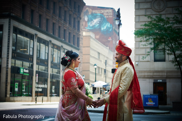 Indian couple holding hands at the street.