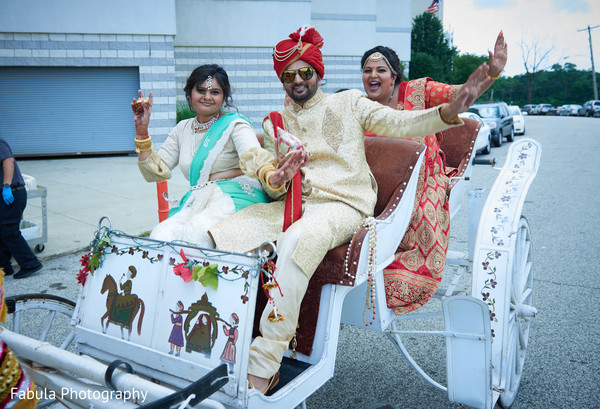 Indian groom in carriage with Indian family.