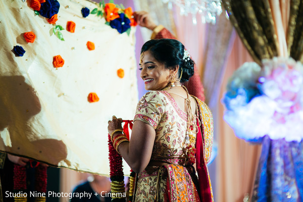Indian bride about to see her groom that is covered by an antarpat.