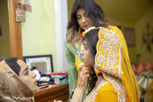 Indian bride getting ready for her haldi party.