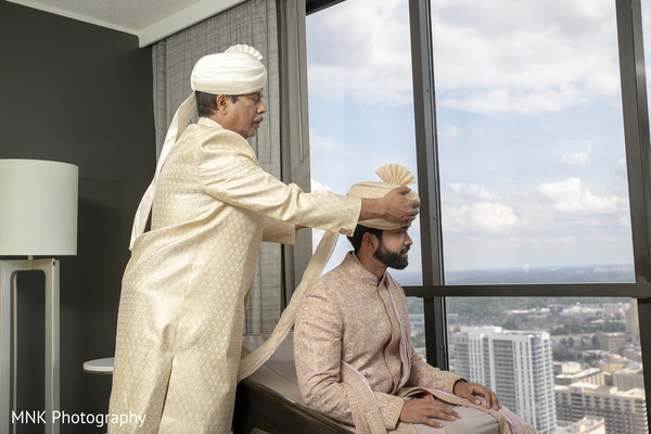 Indian groom being help to put his turban on.