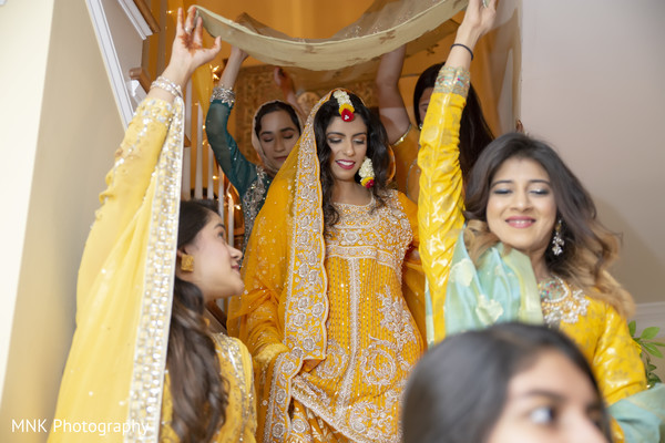Indian bride walking down the stairs on her yellow gown.