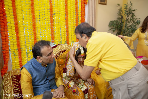 Indian relatives blessing bride at her haldi rituals.