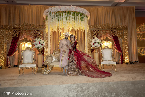 Indian couple posing at their wedding mandap.