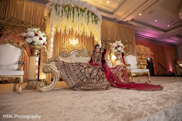 Indian bride sitting on her Indian wedding reception stage.