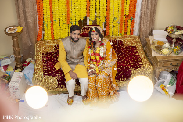 Indian couple posing on their haldi outfits.