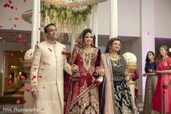 Indian bride walking in to her wedding ceremony with parents.