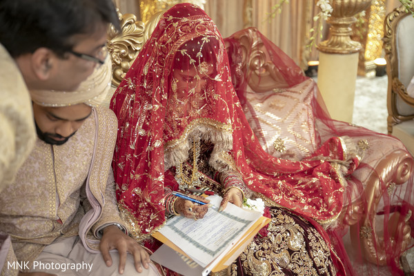 Indian couple signing their wedding contrats.