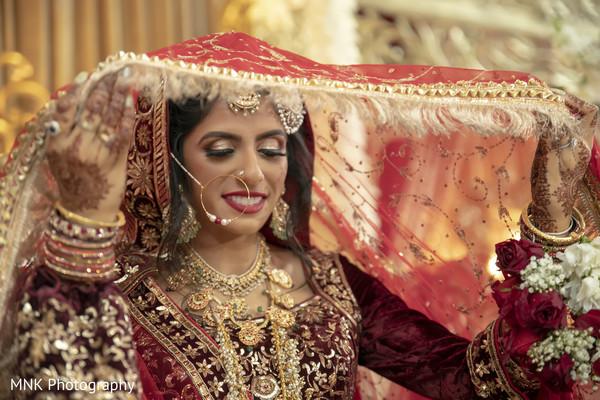 Indian bride taking off her ghoonghat veil.