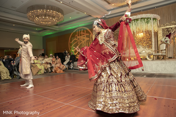 Dreamy Indian couple dancing at reception.