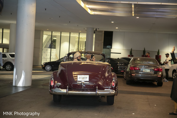 Indian couple leaving on their burgundy cadillac.