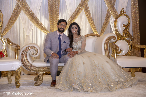 Indian couple posing at reception stage.