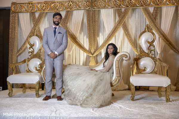 Indian couple posing at their reception stage.