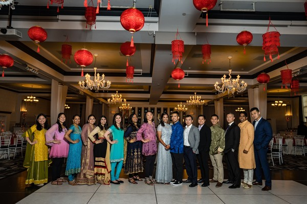 Indian couple posing with bridesmaids and groomsmen.