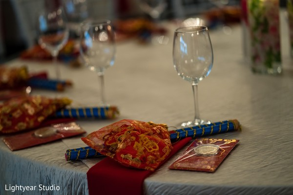 Indian Sangeet table with red golden favors.