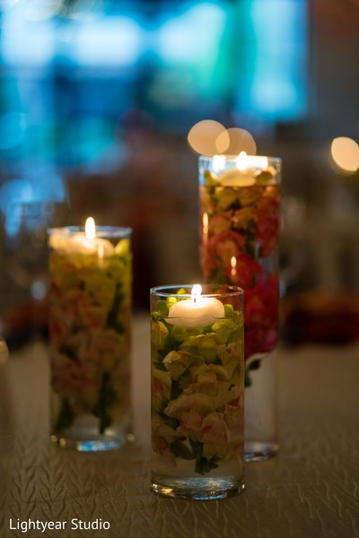 Sangeet table Candle holders full of flowers and water.