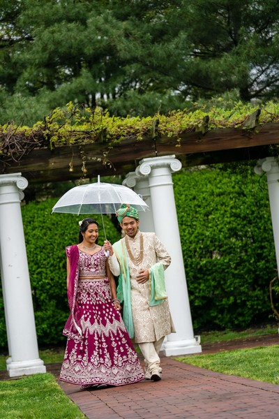 Indian bride and groom walking with their ceremony outfits capture.