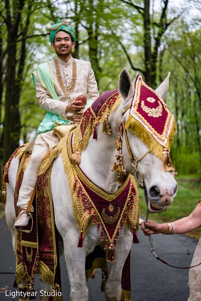 Indian chinese groom on his white baraat horse.