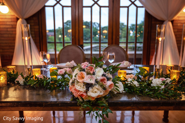 Indian couple's reception table light pink flowers decorations.