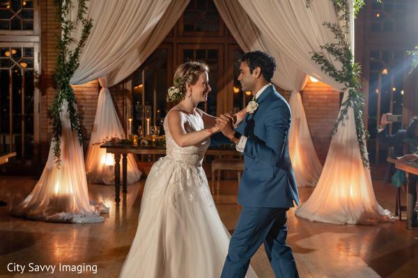 Indian bride and groom dancing at reception dance floor.