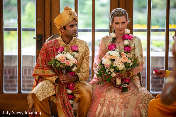 Indian couple holding roses bouquet at wedding ceremony.
