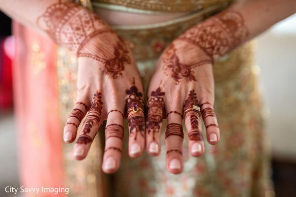 Indian bride showing her brown mehndi art and wedding rings.