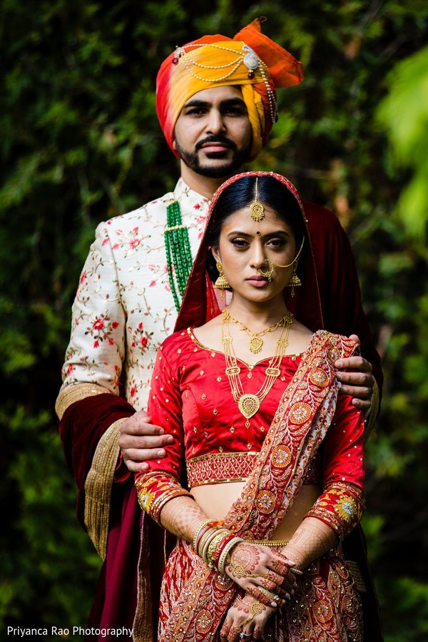 Indian couple with wedding clothes posing for photo.