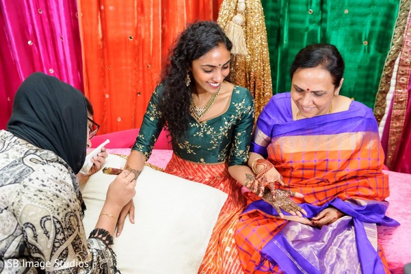 Indian bride with relative looking at her brown henna art.