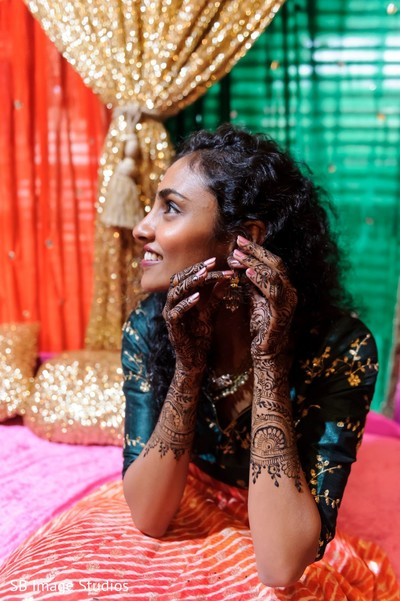Indian bride touching her earrings with her henna decorated hands.