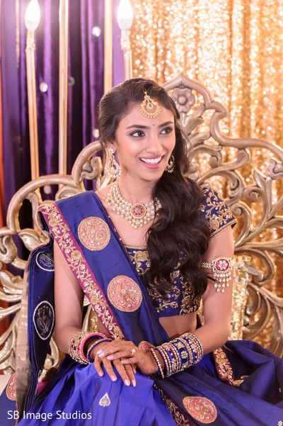 Maharani in a blue anarkali sitting on stage